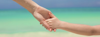 Close-up hands of mother and little kid walking on the beach